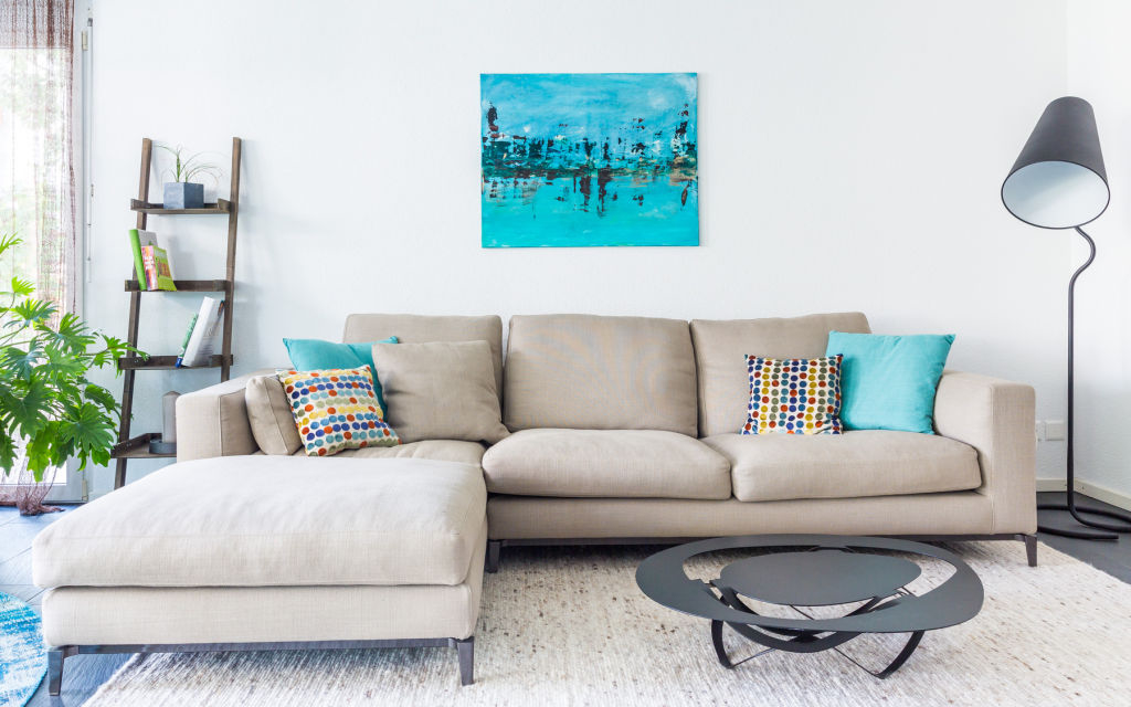 taupe sofa and turquoise art
