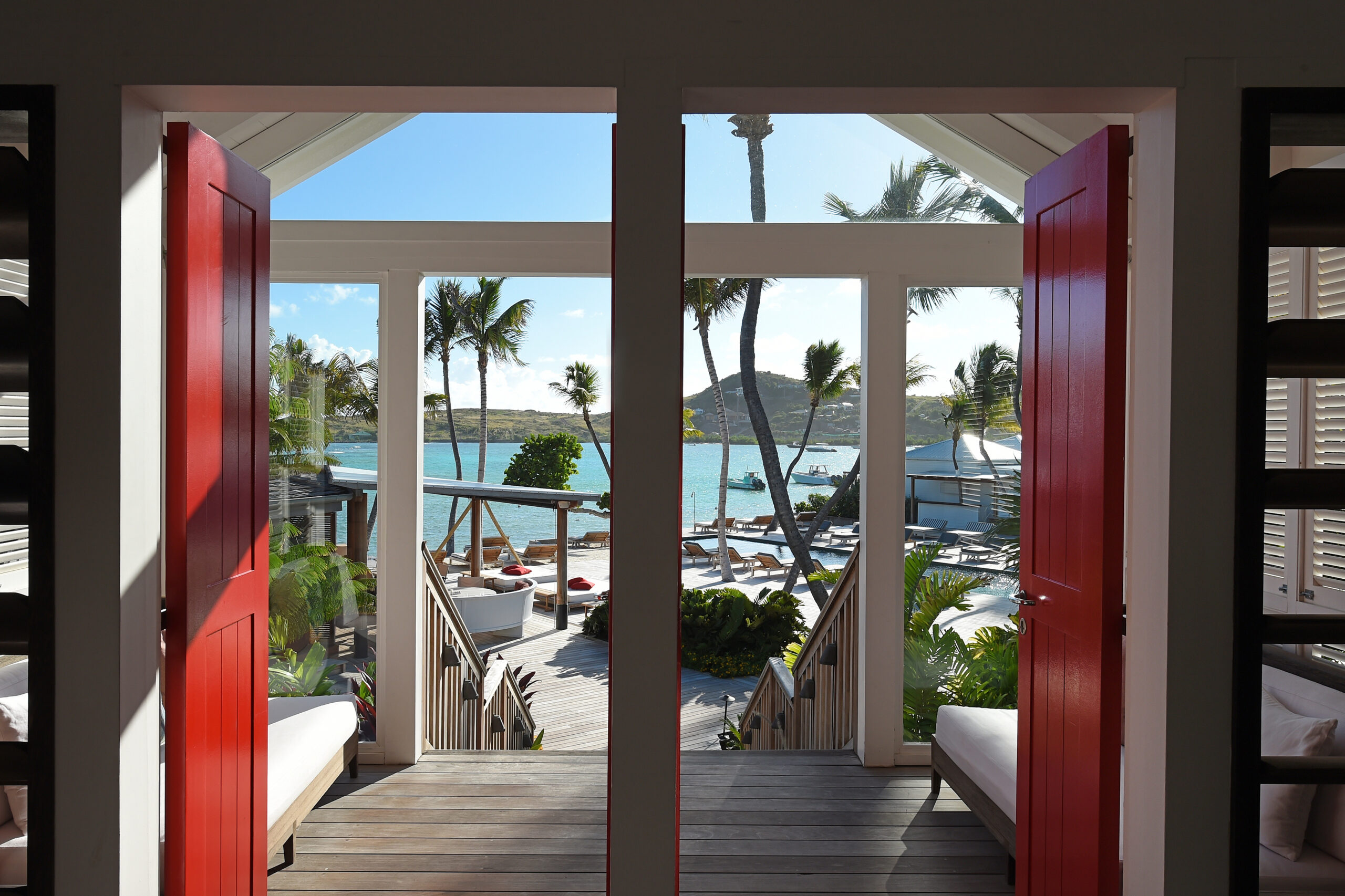 Caribbean architecture with red doors opening onto the ocean