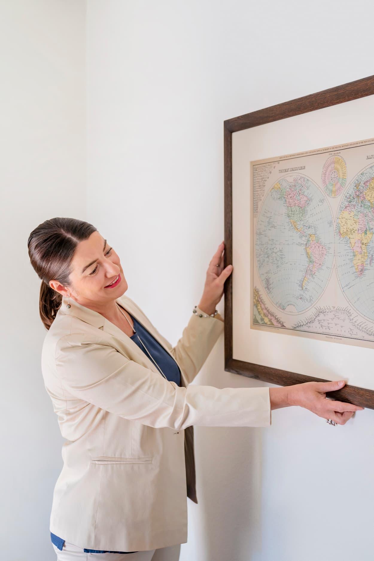 Simone adjusting a framed world map