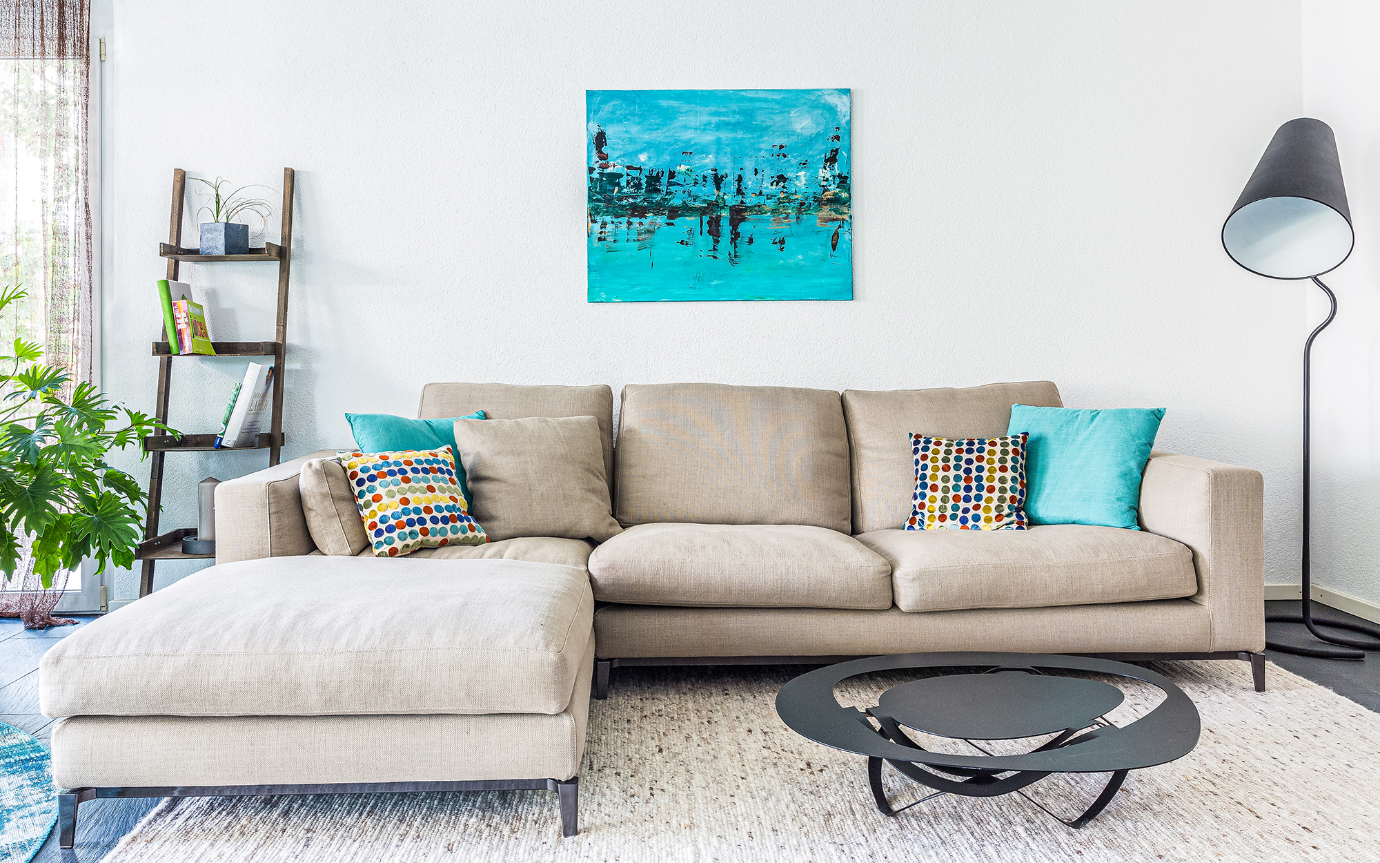 beige sofa and turquoise art